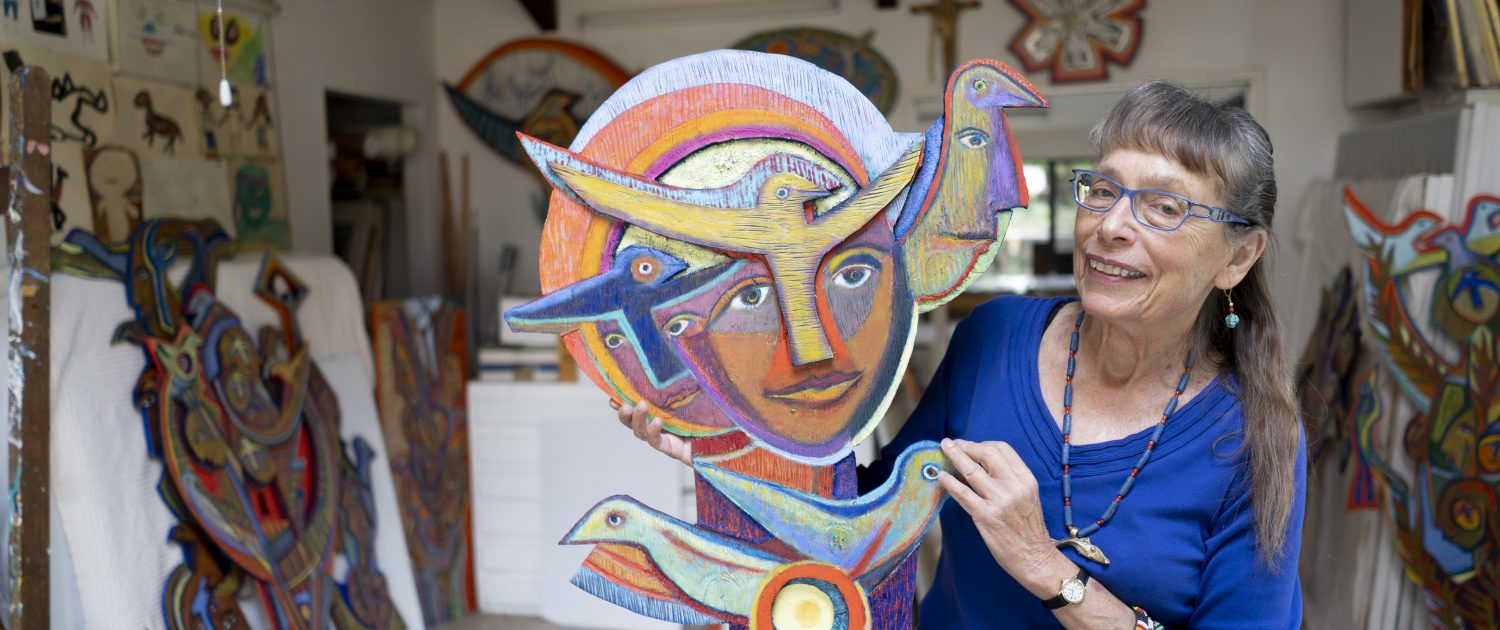Betty LaDuke holding art